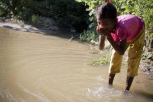 A young girl drinks water straight from a stream  in Bekalalao Village Morondavo, Madagascar. Photo: WaterAid/ Kate Holt