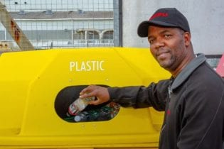 Isuzu employee, Sakhumzi Tsotsi, demonstrates how to dispose of plastic and prevent plastic pollution.